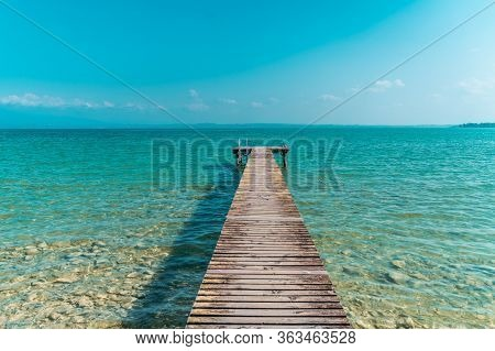 Wooden Dock For Boats On The Light Blue Sea In A Beatiful Sommer Day