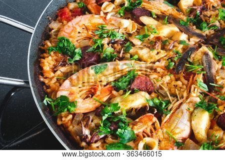 Seafood Paella With King Prawns And Arborio Rice Garnished With Parsley