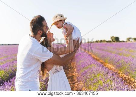 Happy Family Having Fun In A Field Of Flowers.