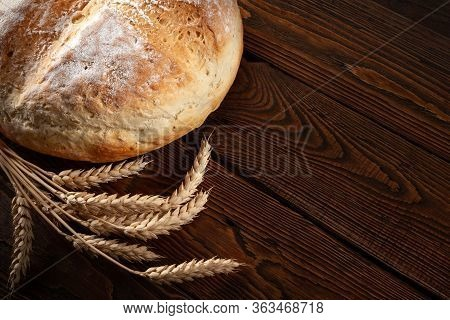 Homebaked Bread. Peasant Round Bread And Wheat Spikelets On A Wooden Background With Space For Text.