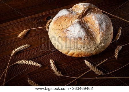 Homebaked Bread. Round Loaf Peasant Bread And Ears Of Wheat On The Wooden Background. Homemade Bakin