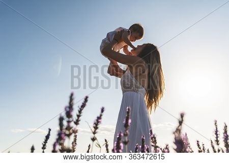 Caucasian Mother Lifting Her Child Under Sunset. Silhouette Of Mother And Son At Sunset. Family Havi