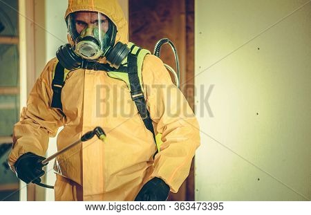 Worker In Hazmat Suit And Full Face Mask Spraying Disinfection Liquid In Order To Kill Bacteria And