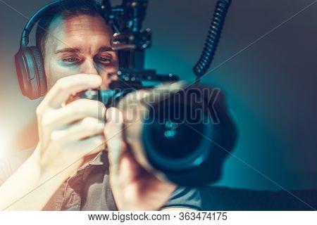 Caucasian Video Camera Operator At His 30s Taking Movie Shots Using Modern Dslr Video Camera. Videog