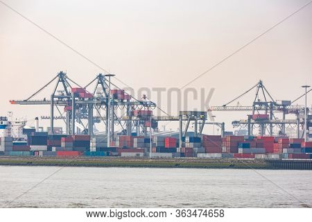 Big Cargo Containers Boat with Goods cargo Stack at the Pier docks port waiting for international sea freight transportation in Rotterdam Port of Netherlands