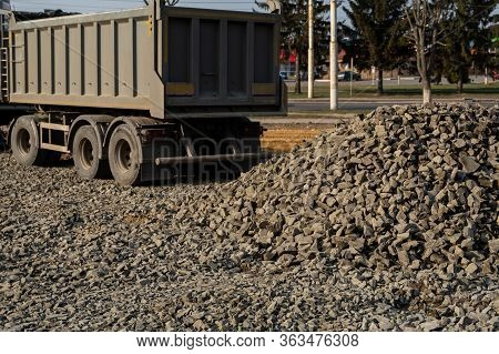 A Dump Truck Is Dumping Gravel On A Construction Site. Dump Truck Dumps Its Load Of Gravel On A New