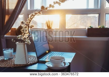 Home Work Place With Laptop, Cup Of Hot Drink And Blooming Brunch In Vase On Coffee Table Near Windo