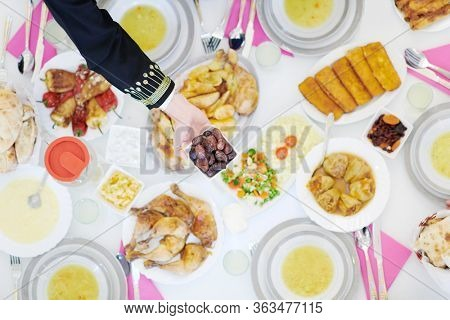 Eid Mubarak Muslim family having Iftar dinner eating dates to break feast. Eating traditional food during Ramadan feasting month at home. The Islamic Halal Eating and Drinking at modern western Islam