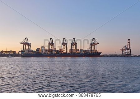Huge container ships in port being loaded in Rotterdam in evening twiligt