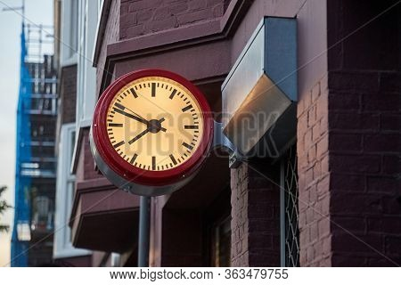 Analogue clock on a wall in an urban street