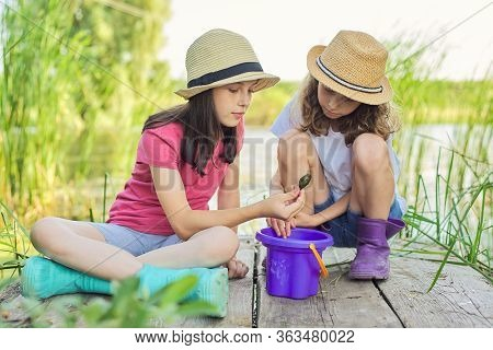 Kids Girls Playing Together On Lake, Sitting On Wooden Pier, Catching Water Snails In Bucket. Childh