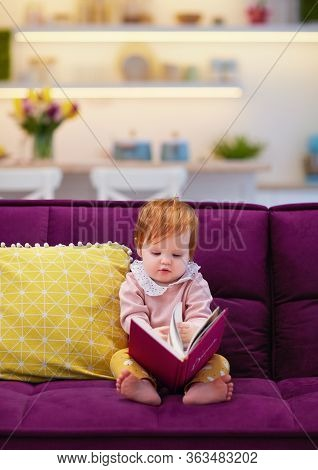Cute Toddler Baby Girl Flipping A Book, Sitting On Sofa In The Livingroom