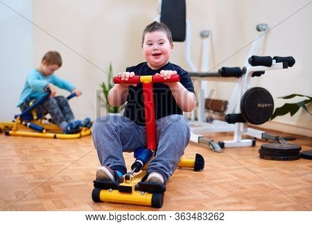 Happy Young Kid With Down Syndrome Exercising On Inclusive Sport Equipment, Developing Muscular Stre