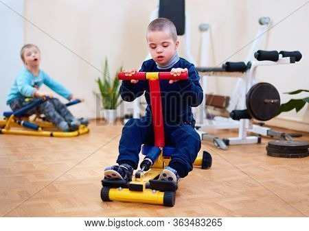 Young Kid With Special Needs Exercising On Inclusive Sport Equipment, Developing Muscular Strength A