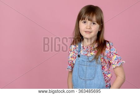 Sweet little girl 6-7 years old posing in dungarees jeans and flower pattern blouse on pink background. Isolateded studio portrait.