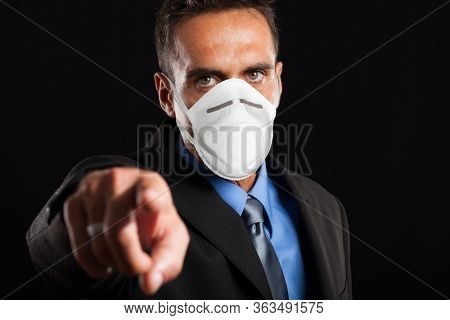 Confident masked businessman pointing his finger at you, coronavirus pandemic hiring concept