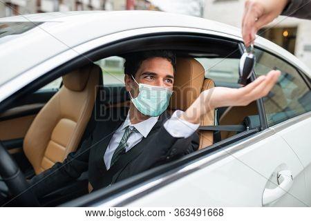 Masked man taking the car keys, automotive coronavirus concept