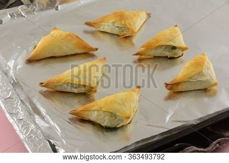 Closeup Of Baked Spanakopita Pastry Appetizers On Aluminum Foil On Baking Sheet