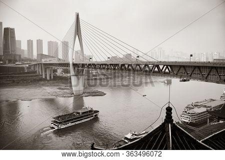 Boat pass below bridge with city urban architecture in Chongqing, China.