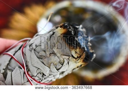 A Close Up Image Of A Hand Holding A Burning White Sage Smudge Stick.