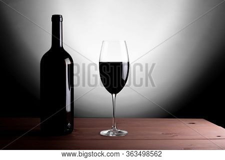 Black Bottle Of Red Wine And A Glass. A Bottle Of Wine Stands On A Table, A Bottle On A Gray Backgro