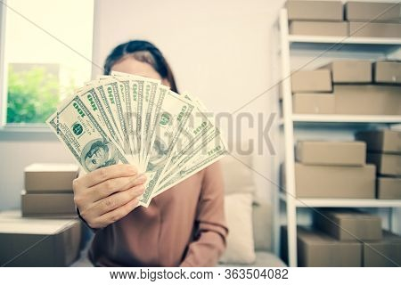 A Young Woman Doing Business Online Holds Money. Glad To Succeed. Startup Concept, Small Entrepreneu