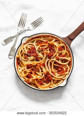 Traditional Italian Roman Pasta - Bucatini With Amatricana Tomato Sauce In A Cooking Pan On A Light