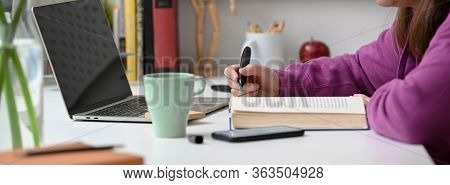 Side View Of College Student Reading Book To Prepare Her Seminar On White Table