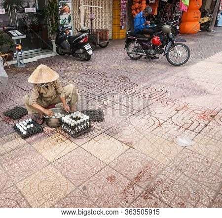 Saigon Vietnam - October 12 2013; Egg Vendor  Woman In Conical Hat Sitting On Low Stool On City Pave