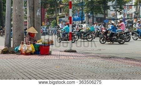 Saigon Vietnam - October 12 2013; Woman In Conical Hats Sitting On Busy Street Corner Surrounded By