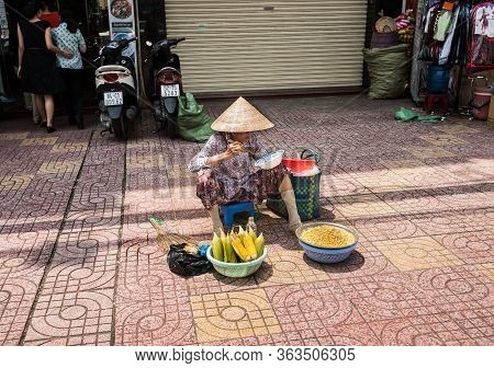 Saigon Vietnam - October 12 2013;   Woman Selling And Eating Corn In Conical Hat Sitting On Low Stoo