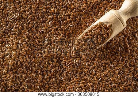 Flax Seed Plant With Brown Linseed In Wooden Scoop For Organic Oil On Dark Stone. Linseed, Flaxseed