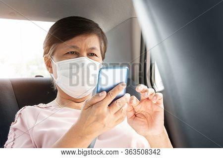 Asian Senior Woman Passenger Wear Surgical Mask For Prevent Coronavirus Or Covid-19 Using Smartphone