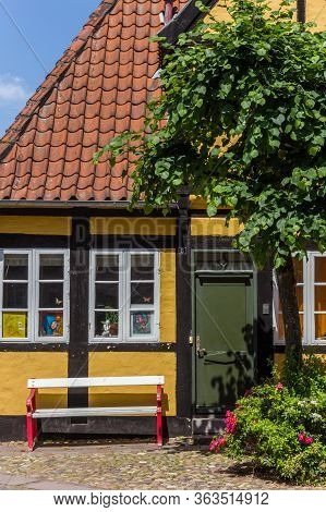 Ribe, Denmark - June 26, 2019: Old Half Timbered House With Bench In Ribe, Denmark