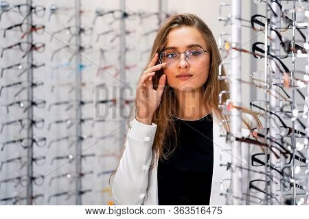 Row Of Glasses At An Opticians. Woman In Spectacles. Stand With Glasses In The Store Of Optics. Show