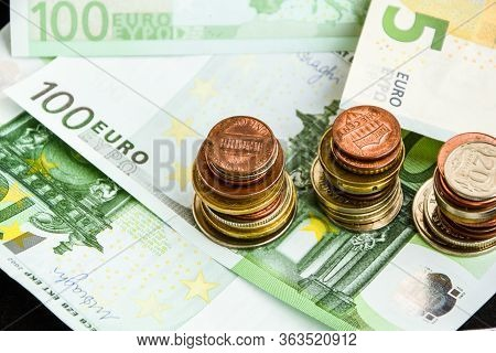 Euro Coins On Banknote Money Background, A Coin On The Background Of Stacks Of Coins And Banknotes