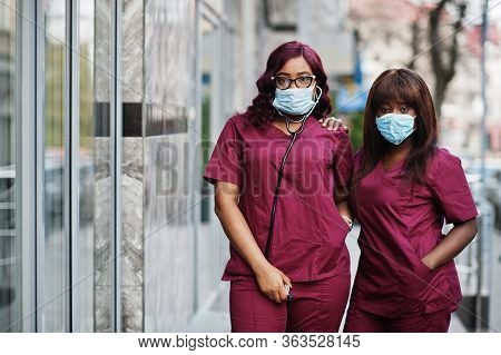 Two African American Female Doctors At Red Lab Uniform In Protective Facial Mask. Medicine, Professi