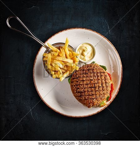 Big Cheeseburger With French Fries And Garlic Sauce On Dark Background