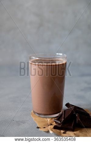 Glass Of Tasty Chocolate Milk On Gray Table. Dairy Cacao Drink