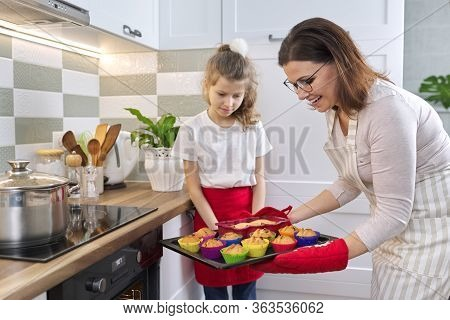 Mother In Apron And Daughter Little Helper Preparing Cupcakes Together. Woman Taking Out Tray With B