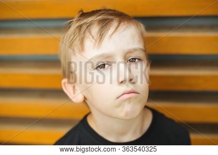 Kid Having Grumpy Dissatisfied Facial Expression. Child Being Grounded By Parents For Bad Behavior.