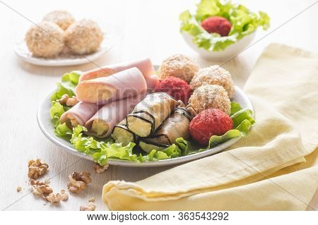 Assorted Cheese In Color Breading Served On A Plate With Yellow Napkin. Cheese With Eggplant. Cheese