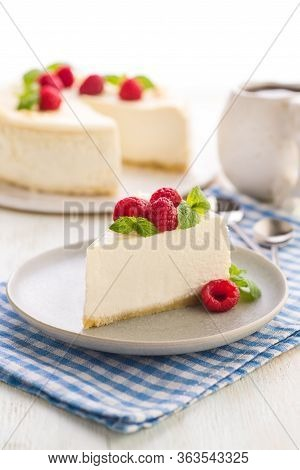 Cheesecake. Traditional American Dessert. A Large Piece Of Cake With Raspberries And Fresh Mint Leav