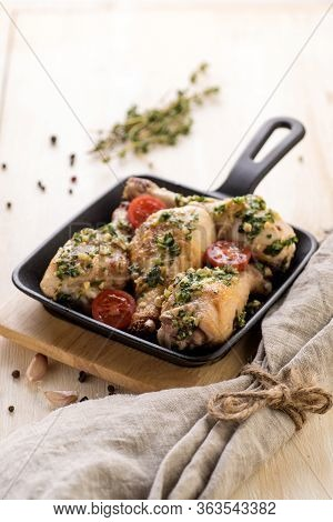 Fried Chicken In Pesto Sauce With Fresh Herbs And Cherry Tomatoes. Cooked In An Individual Cast-iron