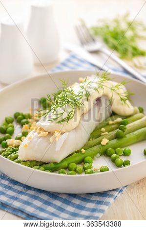Steamed White Fish Fillet With Asparagus And Green Peas And Thick Sauce. A Large Portion Is Served O