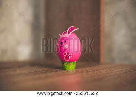 Easter Egg In The Form Of A Pink Rabbit On A Wooden Table