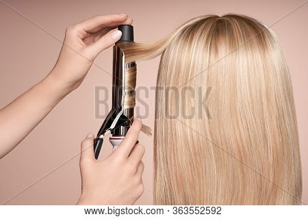 The Hairdresser Curls Long Hair With A Curling Iron. Beautiful Woman With Long Straight Hair. Smooth