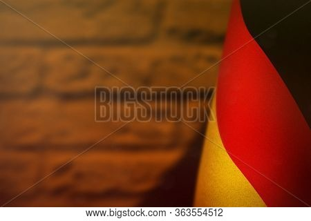 Germany Hanging Flag For Honour Of Veterans Day Or Memorial Day On Orange Blurred Painted Brick Wall