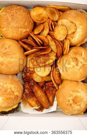 Large box of burgers, fried potato slices and spicy chicken wings.