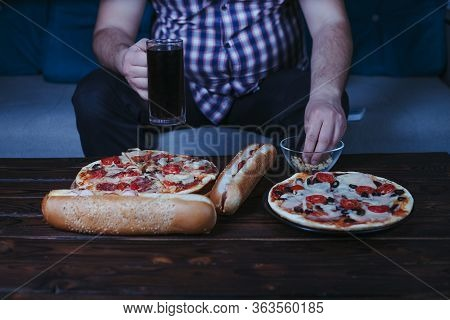 Emotional Eating Mental Disorder, Depression, Stress. Overweight Man Sit On The Coach With Big Amoun